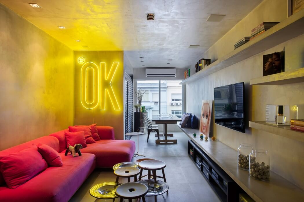 soggiorno in stile pop e industrial con scritta luminosa e me nsole in resina