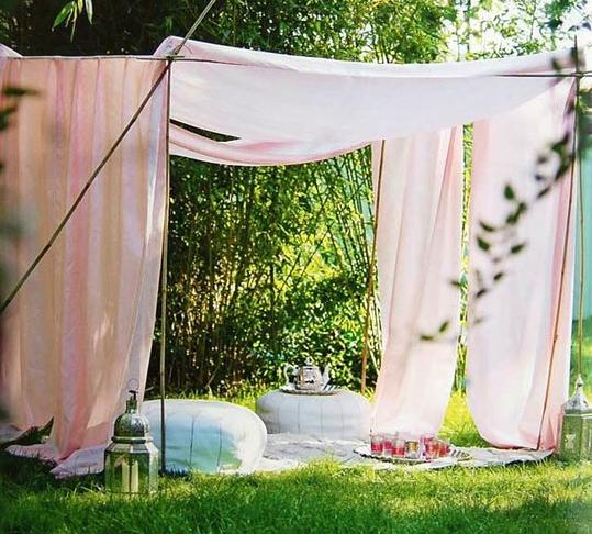 Picnic su prato con tenda rosa cipria e cuscini