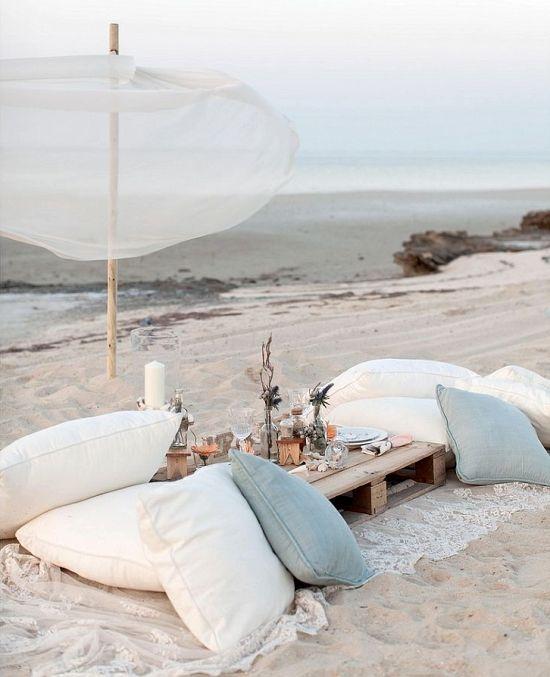 picnic sulla spiaggia con cuscini bianchi e azzurri